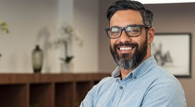 Portrait of happy mature businessman wearing spectacles and looking at camera. Multiethnic satisfied man with beard and eyeglasses feeling confident at office. Successful middle eastern business man smiling in a creative office.